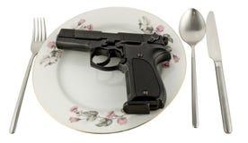 Pistolet dans une plaque sur la table servie Photos stock