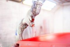 Pistolet de pulvérisation et travailleur peignant une voiture image libre de droits