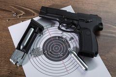 Pistolet pneumatique noir (pistolet pneumatique) contre une table en bois Photos libres de droits