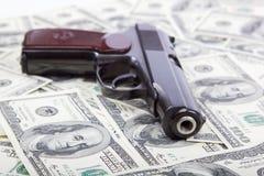 Pistolet przeciw dolarowym rachunkom. Obrazy Stock