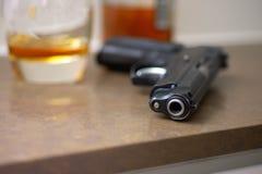 Pistolet, szkło, butelka na stole Zdjęcie Royalty Free