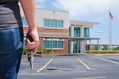Pistolety w szkolnym młodym człowieku z pistoletem przy szkołą