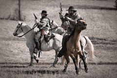 Pistols raised. Two horseback shoulders with raised pistols drawn in the Battle for Round Mountain Royalty Free Stock Photography