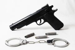 Pistolvapen och handbojor Arkivbild