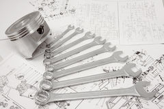 Piston and spanners. Piston and nut keys of different sizes lay on drawing stock photo