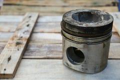 Pistone del motore su fondo di legno, industria dei ricambi auto e fondo dei pezzi di ricambio, danno del pistone nei duri lavori Fotografia Stock Libera da Diritti