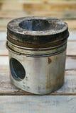 Pistone del motore su fondo di legno, industria dei ricambi auto e fondo dei pezzi di ricambio, danno del pistone nei duri lavori Fotografie Stock