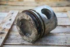 Pistongen av motorn på träbakgrund, automatisk särar bransch- och reservdelbakgrund, pistongskada i hårda arbeten Royaltyfri Bild