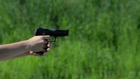 Pistool die op groene achtergrond schieten stock footage