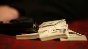 Pistool en drie pakken dollars op de lijst met een rode doek stock videobeelden
