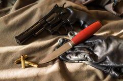 Pistool, mes en handschoenen Pistool en kogels Licht en Schaduw stock afbeelding