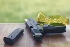 Pistool met veiligheidsbril op een houten achtergrond stock afbeeldingen