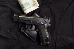 Pistool, portefeuille en geld Het kopen van een wapen stock foto