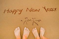 Pisze szczęśliwego nowego roku na plaży kochanek zdjęcia stock