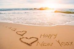 Pisze szczęśliwego nowego roku na plaży z sercami zdjęcie stock
