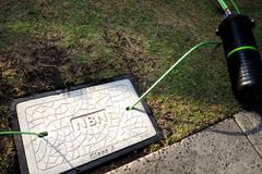Pit with a concrete man hole cover displaying the NBN word mark with fibre optic cables in and out and a dome closure. Melbourne, Australia - May 14, 2018: Pit stock image
