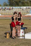 Pit lane girls getting ready for a competition. Rivne, Ukraine - 29 August 2015: Pit lane girls getting ready for a competition on the Open Cup Speedway to the Royalty Free Stock Photos
