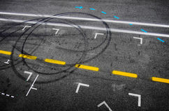 Pit Stop Asphalt. Top view of the asphalt of a car racing pit stop with painted signs and tire marks Stock Photo