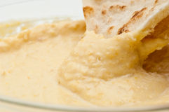 Pita bread dipped in humus Stock Photography