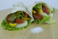 Pita bread with fresh vegetables. Fresh vegetables, tomatoes, onions, peppers, herbs, wrapped in pita bread with a pinch of salt Stock Image