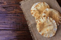 Pita bread isolated on rustic wooden table on rustic cloth. Traditional food of Arabic cuisine. Pita bread isolated on rustic wooden table on rustic cloth royalty free stock photo