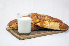 Pita bread with milk. Still life. glass of milk with baked pita bread and cheese on a tray royalty free stock images