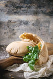 Pita bread. Two homemade whole and sliced pita bread stuffed with fresh basil on wooden cutting board, served with flour over dark table stock images