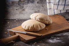 Pita bread. Two homemade wholegrain pita bread on wooden cutting board, served with knife and flour over dark table royalty free stock image