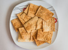 Pita chips in white plate. Homemade spicy pita chips made from pita bread with olive oil and spices in white plate on white background Royalty Free Stock Photos