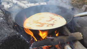 Pita on frying pan on bonfire. Natural healthy food concept. Slow motion stock video