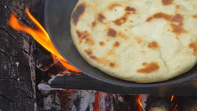 Pita on frying pan on bonfire. Natural healthy food concept. Slow motion stock video footage