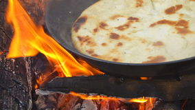 Pita on frying pan on bonfire. Natural healthy food concept. Slow motion stock footage