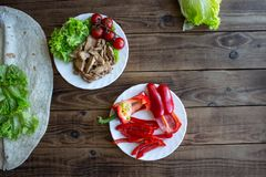 Pita grilled meat tomatoes pepper on a plate and salad on wooden background stock image