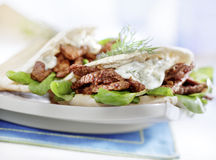 Pita with gyros served on a plate. With lettuce Stock Image