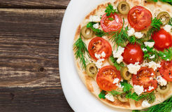 Pita with hummus, cheese, cherry tomatoes, olives and greenery Stock Photography