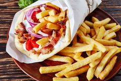 Pita ma gyro on a clay plate. Greek souvlaki, pita ma gyro with chicken meat, vegetables, french fries on a brown plate on a wooden rustic table, view from above stock photo