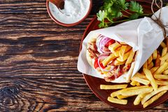 Pita ma gyro on a clay plate. Overhead view of greek souvlaki, pita ma gyro with chicken meat, vegetables, french fries on a brown plate and tzatziki sauce in a stock photos