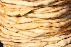 Pita. Pile of roasted pita, baked flat bread. Heap of focaccia. Lavash. Purlenka. Bread background. Flat bread background texture. Stock Image