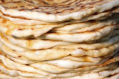 Pita. Pile of roasted pita, baked flat bread. Heap of focaccia. Lavash. Purlenka. Bread background. Flat bread background texture. Stock Photos