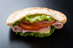 Pita sandwich. Fresh pita ham sandwich on a black table stock photography