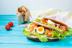 Pita sandwich stuffed with chicken, egg, salad, cheese, cherry tomato on blue wood Royalty Free Stock Photos