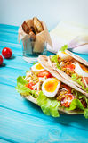 Pita sandwich stuffed with chicken, egg, salad, cheese, cherry tomato on blue wood Stock Images