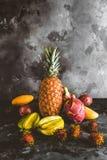 pitaya、红毛丹、阳桃、芒果、番木瓜和西番莲果在大理石桌面 免版税库存图片