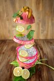 Pitaya or dragon fruit cut into slices which are flying. On a wooden background Royalty Free Stock Photography