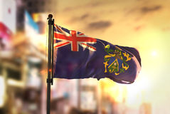 Pitcairn Islands Flag Against City Blurred Background At Sunrise Stock Images