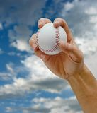 The pitch. Mans hand gripping a hardball about the throw a pitch, sky and clouds in the background Royalty Free Stock Photos