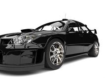 Pitch black modern touring car - front wheel closeup shot Stock Images