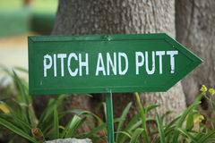 Pitch and Putt signpost. Wooden hand painted green and white Pitch and Putt signpost on a golf course with a right pointing arrow at the base of a tree outdoors Stock Image