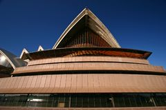 Pitched and pointy roof with exposed concrete beams and large glass window on pink podium of Sydney Opera House Australia. Exterior sloped roof with large royalty free stock photo
