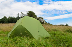 Pitched tent in meadow with big rock in background Stock Images